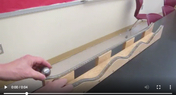 still from a video showing someone putting two small metal balls each on two tracks, one of which is flat except at the very beginning, and the other of which is wavy