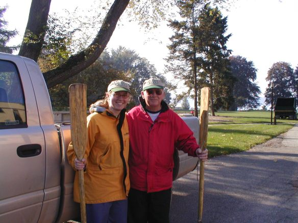 A young woman and an older man standing next to a truck in rain gear, each holding an oar
