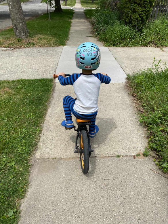 small child in pajamas riding a bicycle with no training wheels, viewed from behind as he pedals down a sidewalk